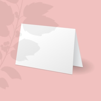 White standing card template with holly berry branch with leaves overlay shadow.