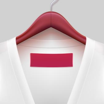 White t-shirt with label hanging on a hanger.