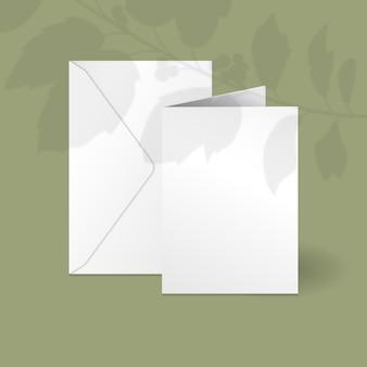 Белая вертикальная карточка и шаблон конверта с веткой ягод падуба с тенью наложения листьев.