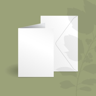 White vertical card and envelope template with holly berry branch with leaves overlay shadow.