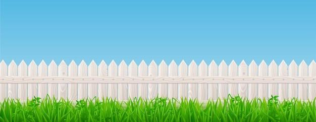 白い木製のピケットフェンスと緑の草