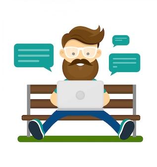 Молодой хипстерский человек с бородой и очками, сидящими на скамье с ноутбуком и использующим интернет wi-fi для беседы с друзьями.