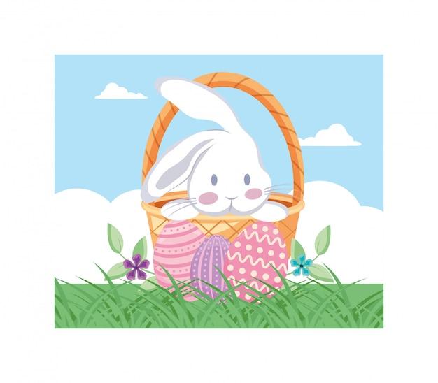 Плетеная корзина с разноцветными пасхальными яйцами и кроликом