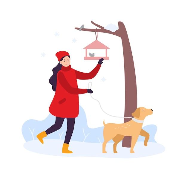 겨울 활동. 강아지와 함께 걷고 새들에게 먹이를 주는 소녀. 겨울 옷을 입은 여성 캐릭터는 애완동물과 함께 야외에서 시간을 보낸다. 새 벡터 일러스트와 함께 나뭇가지에 매달려 피더