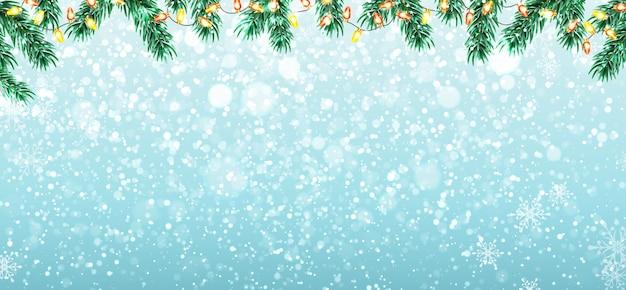Зимний фон с ветвями елки, снегом и огнями гирлянды.