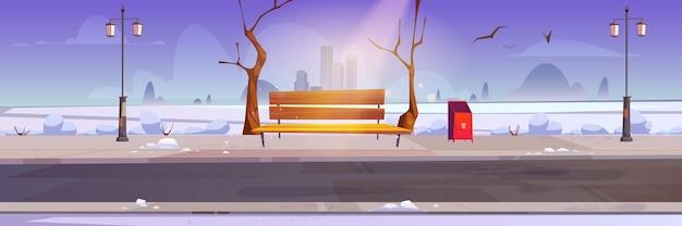 白い雪の木製ベンチとスカイラインの町の建物と冬の都市公園