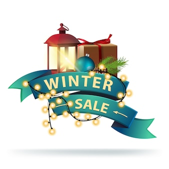 Winter discount banner in the form of blue ribbon wrapped with garland.