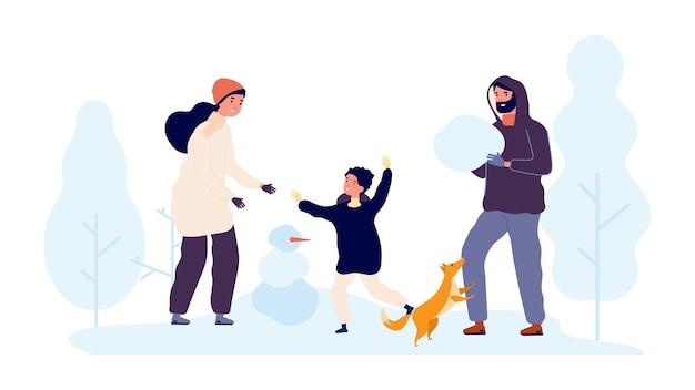 겨울 야외 활동. 가족은 눈 덮인 공원에서 눈사람을 만듭니다.