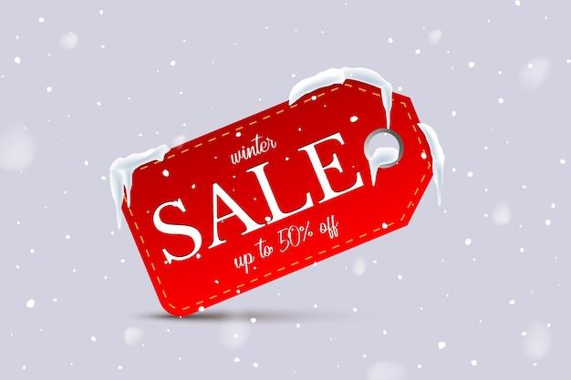 Текст зимней распродажи на красной бирке на фоне снегопада.
