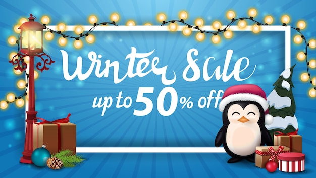 Winter sale, up to 50 off, blue discount banner with white frame wrapped with garland, old pole lantern and penguin in santa claus hat with presents