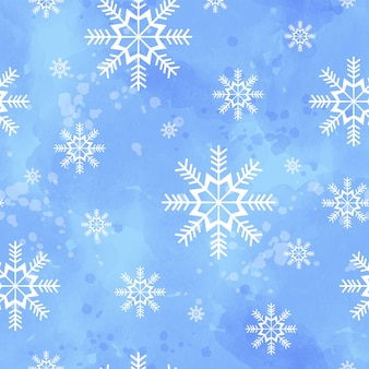 Winter seamless pattern with snowflakes on a blue watercolor background.