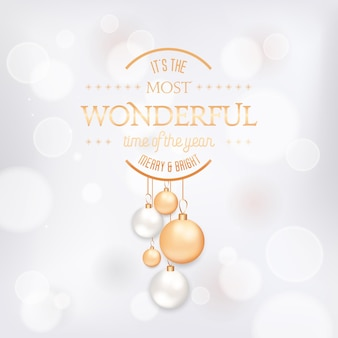 Winter season holidays elegant greeting card with xmas balls. festive decoration in white and gold colors on blurred background with golden typography. merry christmas, new year holiday postcard