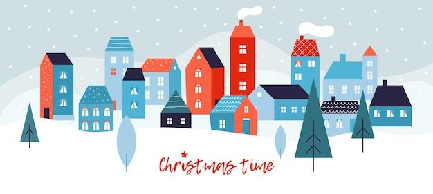 冬のシンプルな風景。かわいい街の建物、雪とモミの木が降る雪に覆われたクリスマスのパノラマ。
