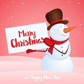 겨울 눈 더미 배경에 손에 배너와 함께 웃는 눈사람. 즐거운 성탄절 보내시고 새해 복 많이 받으세요