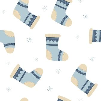 ニットの靴下と雪片と冬のベクトルのシームレスなパターン足のための暖かい服