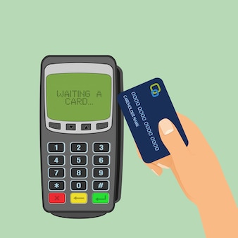 Wireless payment . pos terminal is waiting for card and human hand holding a credit card to pay.