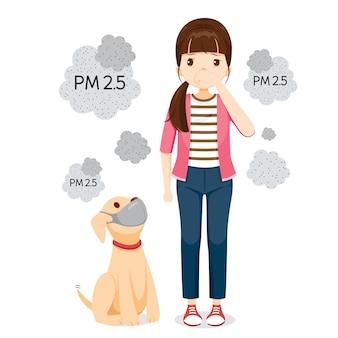 空気汚染マスクを身に着けている女性および犬は塵、煙、スモッグを保護します