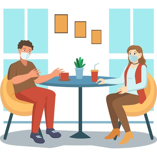 Женщина и мужчина держатся на расстоянии, когда они встречаются в кафе