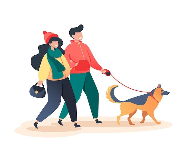 秋の公園で幸せな犬と一緒に歩く女性と男性、ペットケアの概念、ジャーマンシェパード
