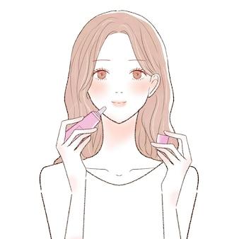 립밤을 바르는 여자. 흰색 배경에.