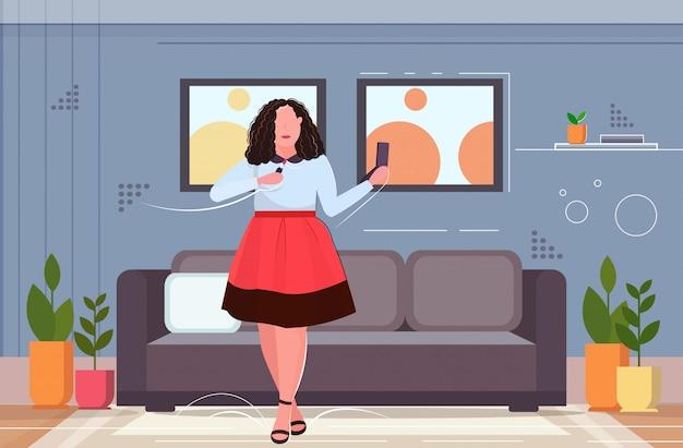 Женщина применение помада смотрит в зеркало избыточный вес девушка делает макияж концепция ожирения современная гостиная интерьер квартира полная длина горизонтальный
