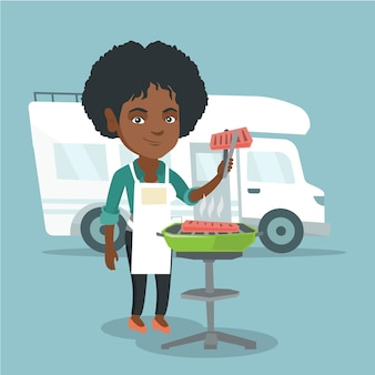 Woman barbecuing meat in front of camper van.