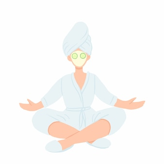 Woman in bathrobe, towel and face mask meditating in lotus pose.