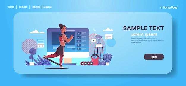 블로그 건강 라이프 스타일 라이브 스트리밍 개념 현대 체육관 인테리어 가로 전체 길이에 대한 저항 밴드 sportswoman vlogger 기록 온라인 비디오와 함께 운동을하는 여자 블로거