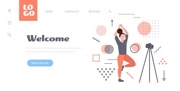 三脚の健康的なライフスタイルのライブストリーミングブログコンセプト水平完全な長さのカメラでオンラインビデオを記録するヨガの練習を行う女性ブロガー
