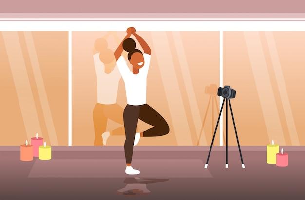 ヨガをやっている女性ブロガースポーツウーマン三脚にカメラでオンラインビデオを記録する健康的なライフスタイルのライブストリーミングブログコンセプトモダンなジムインテリア水平全長