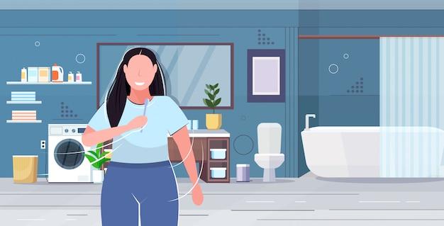 Ключевые слова на русском: женщина чистить зубы избыточный вес девушка держит зубная щетка ожирение концепция современная ванная комната интерьер плоский портрет горизонтальный