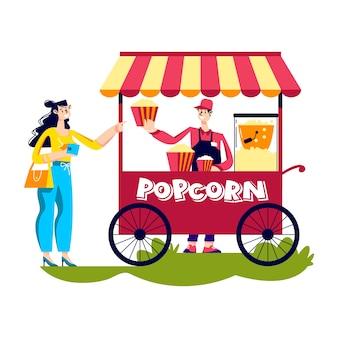 Woman buy popcorn in street kiosk.