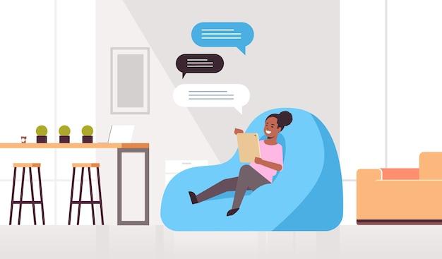 モバイルアプリのソーシャルネットワークチャットバブル通信を使用して豆袋に座っているメッセージングアフリカ系アメリカ人の女の子のチャットの女性