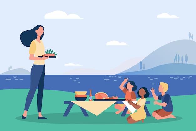 Donna e bambini che hanno picnic vicino al fiume.