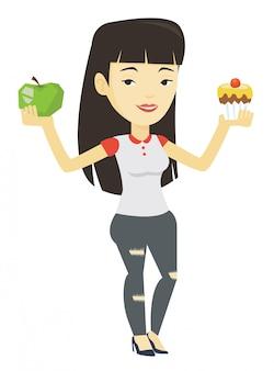 Женщина, выбирая между яблоком и кекс.
