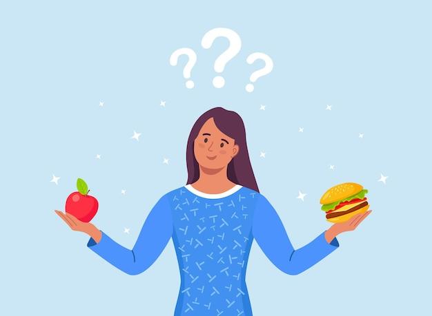 건강에 좋은 음식과 건강에 해로운 음식 사이에서 선택하는 여성. 패스트푸드와 균형 잡힌 메뉴 비교