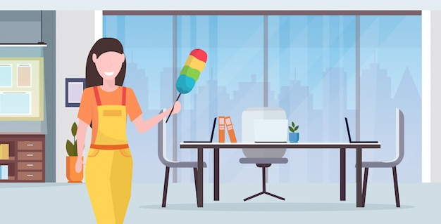 Woman cleaner in uniform holding dust brush female janitor dusting professional cleaning service concept creative co-working center modern office interior portrait flat horizontal