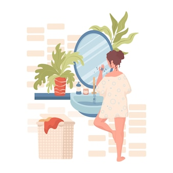 Woman cleansing or moisturizing face in bathroom