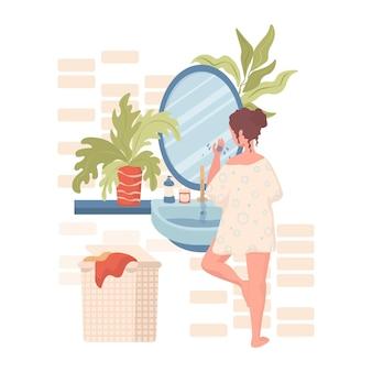 Женщина очищает или увлажняет лицо в ванной комнате