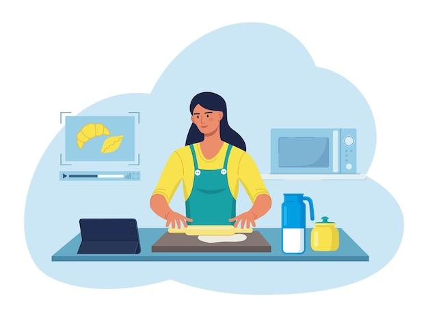 인터넷 비디오를 사용하여 집에서 요리하는 여자. 패스트리와 크루아상을 위한 반죽을 준비하는 웃는 주부 아름다운 아가씨 캐릭터