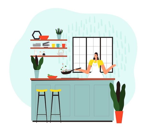 女性は台所の彼女の家で料理をし、フライパンを持っています