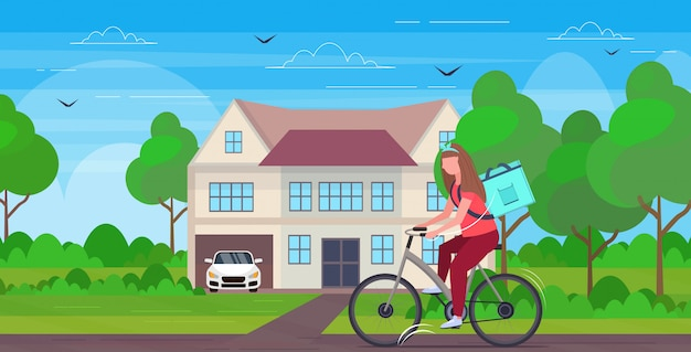 Woman courier with large backpack riding bike delivering food from shop or restaurant express delivery service concept modern villa house landscape background  horizontal full length