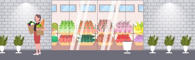 Женщина покупатель держа бумажные мешки полные бакалеи женщина покупатель покупка продуктов покупка концепция современный продуктовый магазин супермаркет экстерьер полная длина горизонтальный баннер