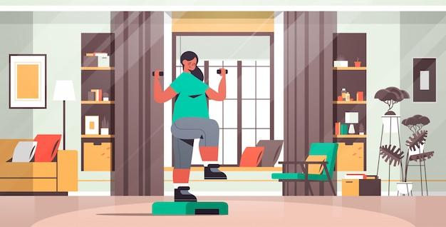 여자 운동 심장 피트니스 훈련 건강 한 라이프 스타일 스포츠 개념 거실 인테리어 전체 길이 그림 데 집에서 단계 플랫폼에서 아령으로 운동을하는 여자