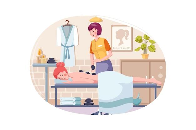 Женщина делает массаж женщине с камнями