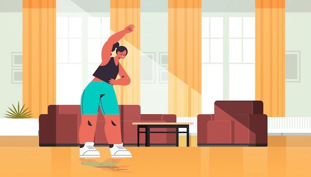여자 운동 심장 피트니스 훈련 건강 한 라이프 스타일 스포츠 개념 거실 인테리어 전체 길이 그림 데 집에서 스트레칭 운동을하는 여자