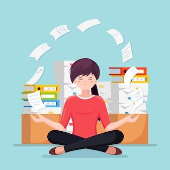 ヨガをしている女性。紙の山、段ボール箱、段ボール箱に書類が山積みで忙しいストレス従業員。瞑想し、リラックスし、落ち着いてストレスを管理する労働者