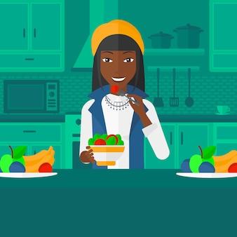 Женщина ест салат.