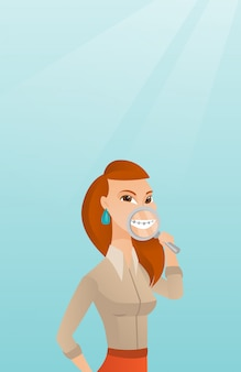 Woman examining her teeth with a magnifier.
