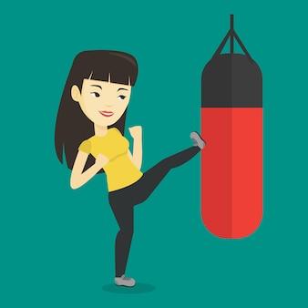 パンチングバッグと運動の女性。